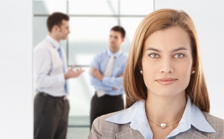 Portrait of attractive, smiling businesswoman, colleagues chatting in background. photo