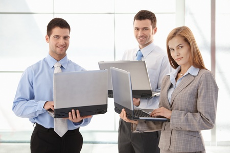 Team of confident businesspeople working on laptop in office lobby, smiling. photo