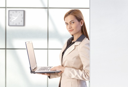 Attractive young businesswoman using laptop, smiling in office. photo