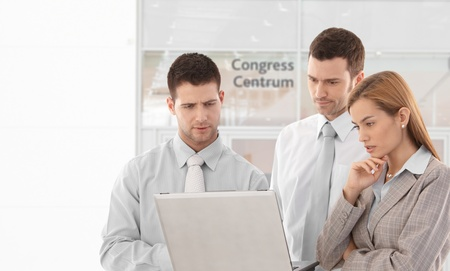 Young corporate team looking at laptop screen, standing in congress center lobby. photo