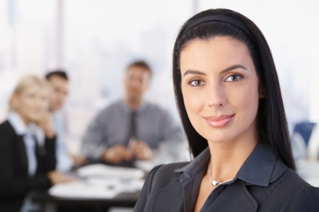 one on one meeting: Portrait of attractive smiling businesswoman, team in background.