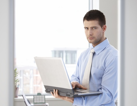 Young handsome businessman working on laptop, standing in bright office. photo