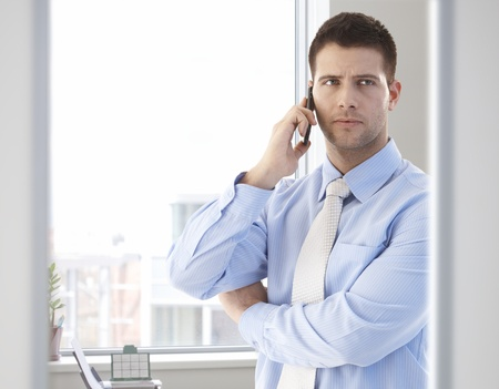 see through: Goodlooking casual office worker talking on mobile phone in bright office.