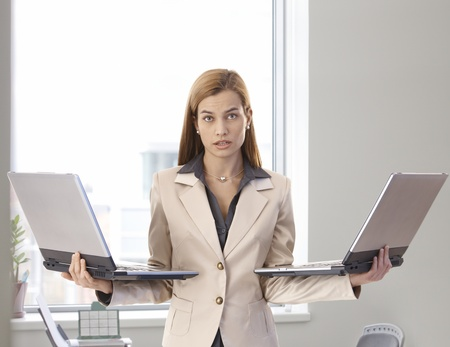 Desperate businesswoman standing in bright office holding two laptops in hands. photo