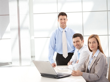 co worker: Successful confident businessteam smiling happily in meeting room.