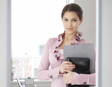 Portrait of young caucasian office worker standing. looking at camera, smiling. Stock Photo - 9066302