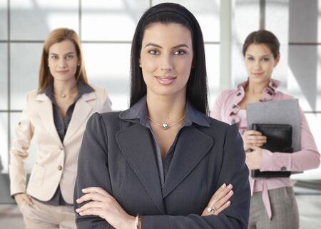 three women: Team portrait of happy businesswomen standing on office corridor, looking at camera, smiling.