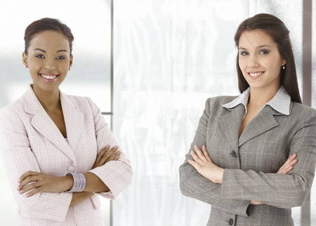Portrait of happy young businesswomen standing on office corridor, looking at camera, smiling. Stock Photo - 9066428
