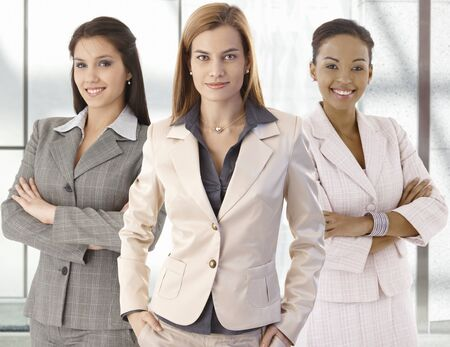 comerciale: Team portrait of happy businesswomen standing on office corridor, looking at camera, smiling.