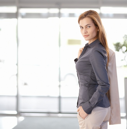 Young businesswoman leaving office, looking back at camera, smiling. Copy space on left. Stock Photo - 9066112