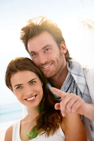 looking away: Happy young couple having fun on summer beach, looking away, smiling. Stock Photo
