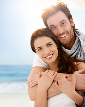 Happy young couple embracing on summer beach, having fun together, laughing. Stock Photo - 9155928