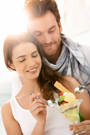 pareja comiendo: Feliz pareja comer helado en la playa de verano, sonriendo.