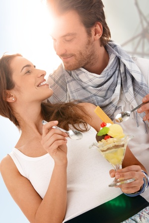 Happy young couple eating icecream together in strong summer sunlight, smiling. photo