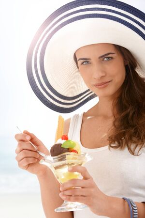 Attractive young woman in summer straw eating icecream, looking at camera, smiling. photo