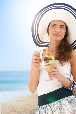 have on: Attractive young woman in summer straw eating icecream on beach, looking away, smiling.