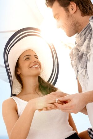 Happy young couple having having engagement on summer beach, looking at each other, smiling. Stock Photo - 9155931