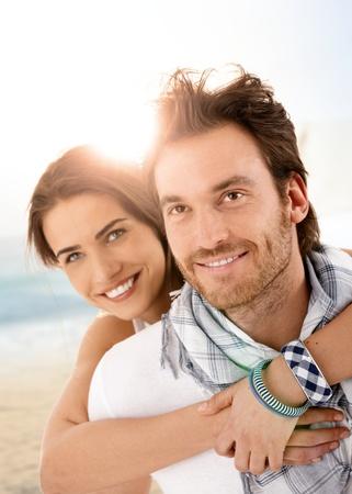 couple enlac�: Heureux jeune couple enlac� sur la plage l'�t�, avoir du plaisir ensemble, en riant.