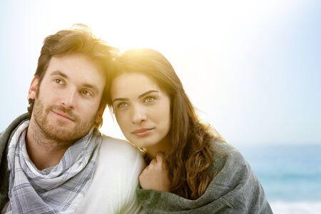honeymoon couple: Young couple sitting on summer beach with blanket enjoying sunset. Stock Photo