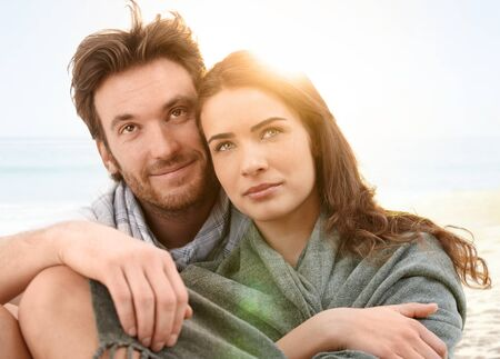 love image: Young couple sitting on summer beach with blanket enjoying sunset. Stock Photo