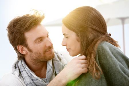 novios besandose: Atractiva pareja joven sentado en la playa bes�ndose en la puesta de sol de verano.