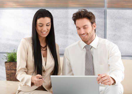 Happy professionals sitting in elegant office, using laptop, smiling. photo