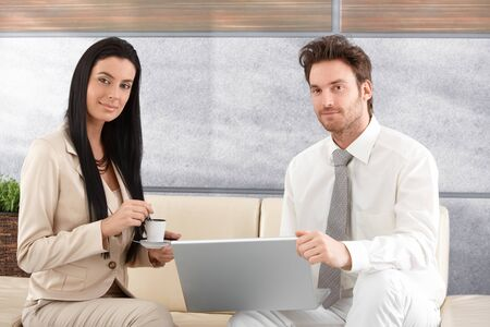 Portrait of attractive businesspeople, sitting in elegant office, using laptop, drinking coffee, smiling. photo