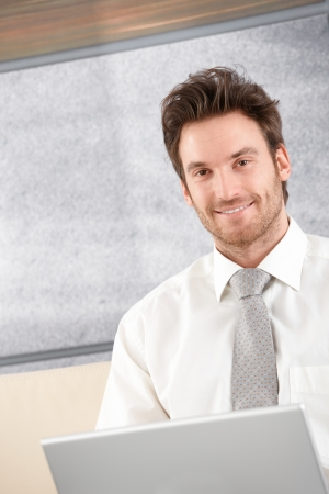 single rooms: Portrait of handsome businessman sitting in elegant office, smiling.