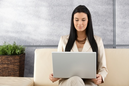 Attractive young woman sitting in elegant office using laptop, smiling. photo