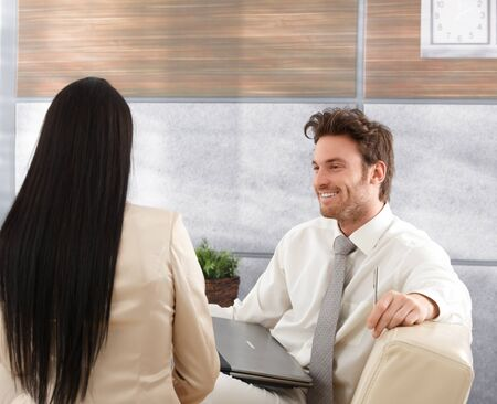 Smiling young businessman sitting in elegant office, talking to female colleague. photo