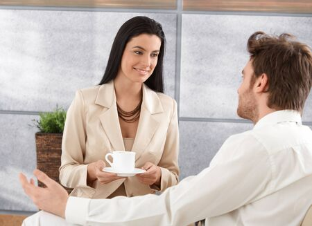 Portrait of pretty businesswoman drinking coffee, talking to male colleague, smiling. photo