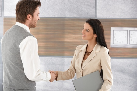 shaking hands business: Attractive young businesspeople shaking hands in modern office, smiling. Stock Photo