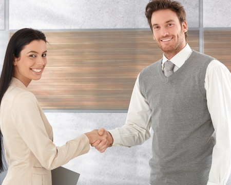 applicant: Attractive businesspeople shaking hands, smiling happily.