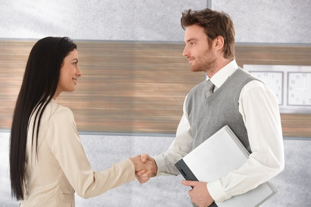 each other: Young businesspeople greeting each other by shaking hands, smiling. Stock Photo