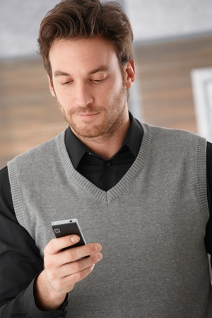 adult texting: Young handsome businessman using mobile phone, writing text message.