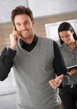 Happy businessman talking on mobile phone, secretary standing behind. Stock Photo - 9201952