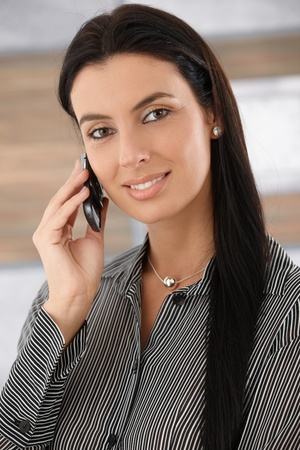 Portrait of beautiful young businesswoman talking on mobile phone, smiling. Stock Photo - 9201954