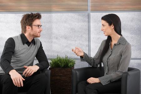 two people talking: J�venes colegas sentado en el vest�bulo de la Oficina, hablando, sonriendo.