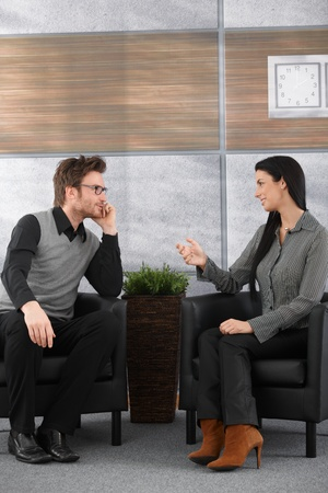 dos personas hablando: Jóvenes socios sentado en el vestíbulo de la Oficina, hablando. Foto de archivo