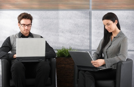 Young businesspeople sitting in office lobby, working on laptop. Stock Photo - 9201901