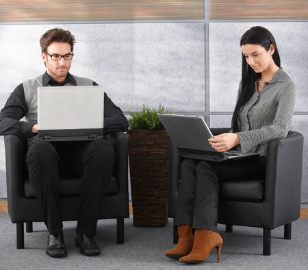 Young professionals sitting in office lobby, working on laptop. photo
