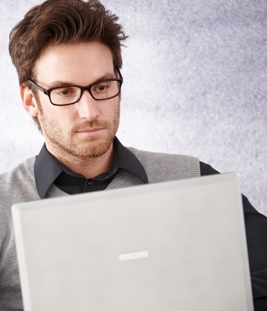 Portrait of young handsome businessman using laptop, wearing glasses. photo