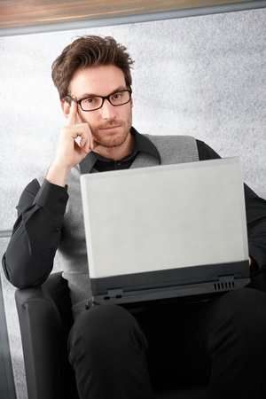 Goodlooking businessman sitting in office lobby, working on laptop. photo