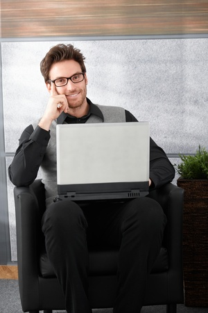 Handsome young businessman smiling, working on laptop, photo
