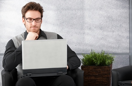 Young businessman sitting in office lobby, browsing internet on laptop. photo