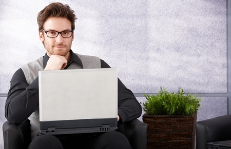 Confident businessman sitting in office lobby, working on laptop, smiling. Stock Photo - 9201831