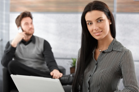 Beautiful young businesswoman working on laptop, smiling at camera, man sitting at background. Stock Photo - 9201915