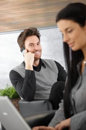 prestar atencion: Ejecutivo joven guapo hablando en mobile, Secretario en segundo plano.