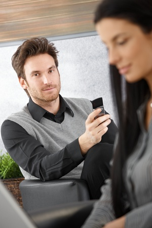 Portrait of handsome young businessman with mobile phone. photo