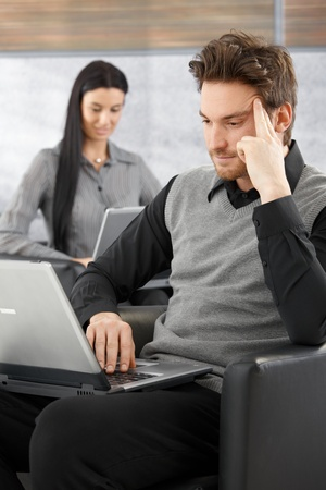 Young businessman sitting in office lobby, working on laptop, woman at background. photo